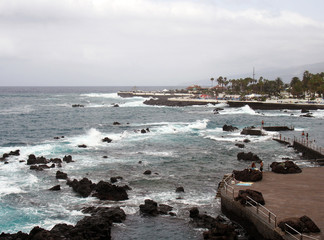 the promenade and lido at puerto de la cruz in tenerife with people on the seafront and dramatic waves breaking over the coastal rocks