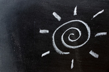 White color chalk hand drawing as sun with light ray shape on black board background