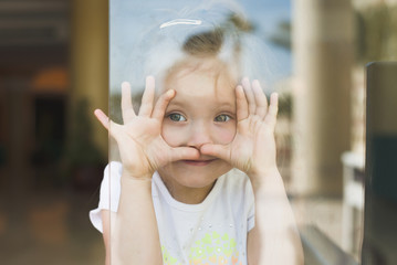 Little girl show emotions in window