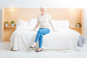 Happiness. Pleasant kind cheerful aged woman smiling and looking happy while being in a beautiful light comfortable room and sitting on a nice soft bed