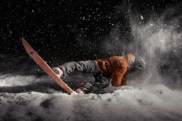 Man snowboarding at night under the snow