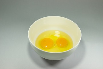 Two eggs in a white bowl on a gray background.