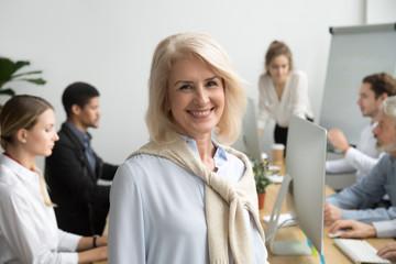 Smiling female aged company executive or team leader looking at camera, happy senior businesswoman teacher coach posing with office people at background, friendly older woman boss head shot portrait