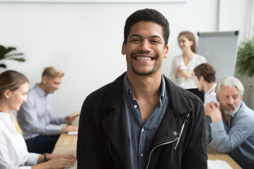 Smiling african american office employee or leader looking at camera with diverse colleagues at background, happy young black manager, professional coach or team member posing, head shot portrait