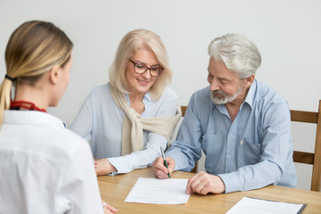 Aged couple signing contract making investment at meeting with financial advisor, happy senior family put signature on business document taking bank loan, retired smiling customers buying insurance