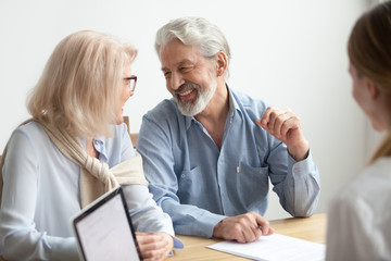Happy senior family talking smiling at meeting with financial advisor, older clients ready to buy medical health life insurance consulting broker, aged retired couple making real estate deal about to