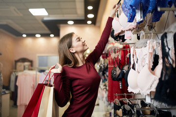 Young woman chooses sexy brassiere among set in a boutique. Pretty girl considers bra with shopping bags in her hand in underwear store.