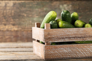 Fresh cucumbers in crate on grey wooden table