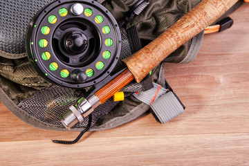 fly fishing rod with a coil and flies lie on old, wooden boards