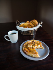 French raisin pastries on a white plate and wicker basket with a cup of coffee on a wooden table