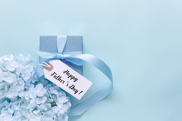 Top view aerial image of decoration Happy Fathers day holiday background concept.Flat lay dad white card with blue flower on modern beautiful  blue paper at home office desk.Free space for design.