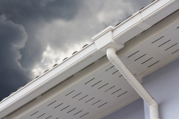 white plastic rain gutter and dark sky. concept : preparing maintenance rain gutter before rainy season..