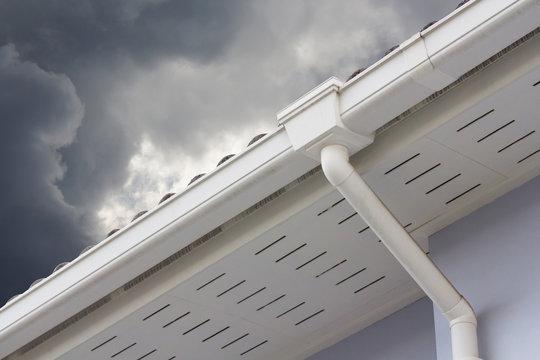 white plastic rain gutter and dark sky. concept : preparing maintenance rain gutter before rainy season..