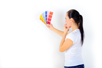 girl with a dreamy look chooses the color of the paint to repair the room, on a white background