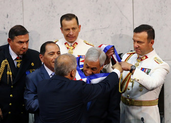 Chile's newly sworn in President Sebastian Pinera receives the sash from President of the Senate Carlos Montes at the Congress in Valparaiso
