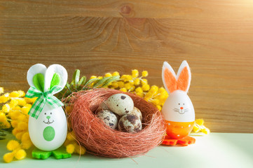 Easter background. Easter bunnies and eggs in the nest near the mimosa flowers