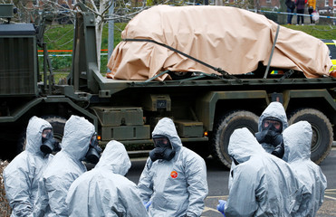 Soldiers wearing protective clothing gather after removing vehicles from a car park in Salisbury