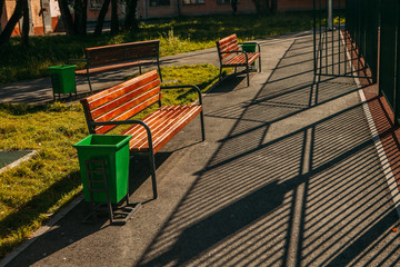 bench with trashcan in park summer outdoor with shadows of fence
