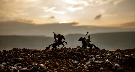 Joust between two knights on horseback. Sunset on background. Selective focus