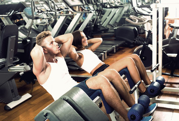 man and woman making sit ups together using machine in gym