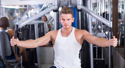 vigorous young man training upper body using fly machine