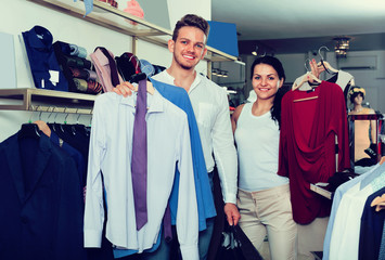 Couple purchasing clothes for two in boutique