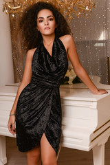 Gorgeous young slim seductive woman with dark curly hair wearing black velvet dress near white piano in luxury interior