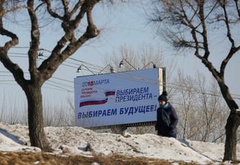 A woman walks past a billboard advertising the upcoming presidential election, in Krasnoyarsk