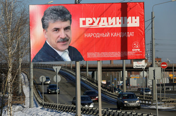 Cars drive past a billboard advertising the campaign of Pavel Grudinin, candidate of the Russian Communist Party in the upcoming presidential election, in Krasnoyarsk