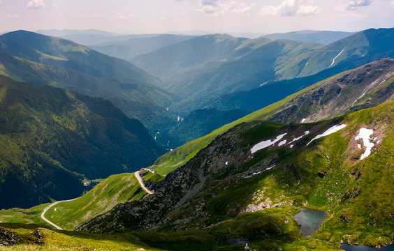 beautiful view in to the valley of fagars mountain. lake among the grassy slopes and rocky cliffs. unforgettable vacation in Romania