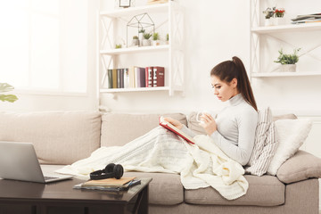 Cozy home. Young thoughtful woman with book