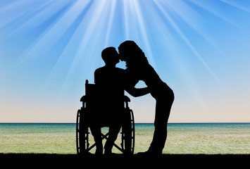 Silhouette of a disabled man in a wheelchair and his wife who is kissing by the sea