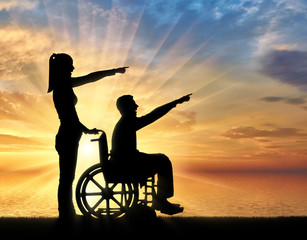 Silhouette of a disabled man in a wheelchair and his wife have a good time by the sea