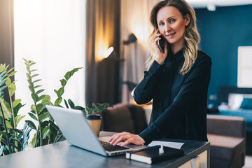 Young smiling businesswoman in black blouse is standing indoor, working on computer, while talking on cell phone. Girl freelancer, entrepreneur works at home.Online marketing, education, distance work