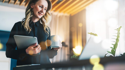Young smiling businesswoman in black blouse stands in front of computer and looks at screen while drinking coffee and holding digital tablet. Girl freelancer works at home. Online marketing, learning.
