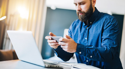 Young smiling bearded businessman sitting at table in front of computer, using smartphone. Freelancer, entrepreneur works at home. Online marketing, education for adults, distance work.