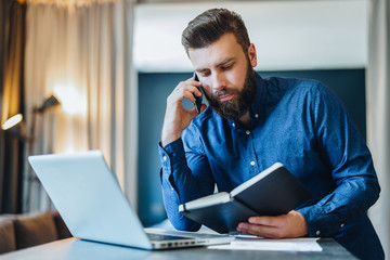 Young bearded businessman is sitting in front of computer, talking on cell phone while looking in notebook. Freelancer, entrepreneur works at home. Telephone conversations. Distance work, education.