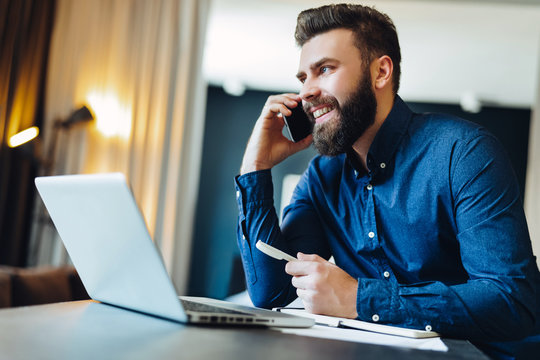 Young smiling bearded businessman is sitting at table in front of computer, talking on cell phone, holding pen. Freelancer works at home. Telephone conversations. Distance work, online education.