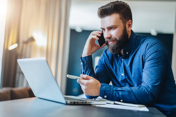 Young smiling bearded businessman is sitting at table in front of computer, talking on cell phone, showing pen on laptop screen. Freelancer works at home. Distance work, online education, marketing.