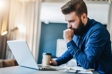 Young serious bearded businessman working on computer at table, drinking coffee, thinking. Man analyzes information, checking email. Freelancer working at home.Online marketing, education, e-learning.