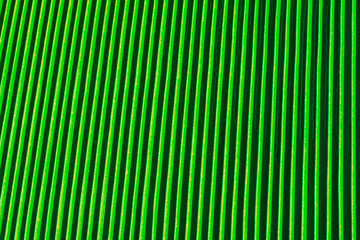 Abstract background of vertical relief metal ribs covered with green color