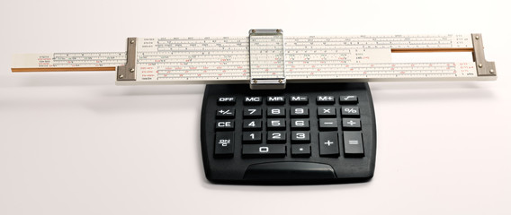 Classic slide ruler on an electric calculator on a white background