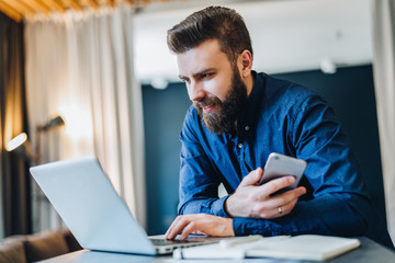 Young smiling bearded businessman in dark blue shirt is working on computer holding smartphone. Man checking email, browsing internet, planning. Online marketing, education, e-learning, e-commerce.