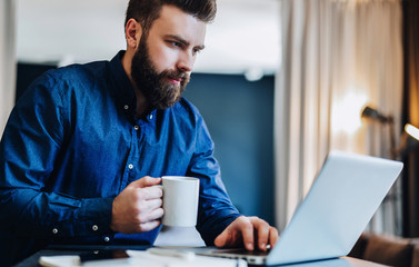 Young serious bearded businessman working on computer at table, drinking coffee. Man analyzes information, data, develops business plan. Freelancer working. Online marketing, education, e-learning.