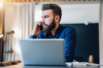 Front view. Young bearded businessman is sitting at table in front of computer, talking on cell phone. Freelancer, entrepreneur works at home. Telephone conversations. Distance work, online education.