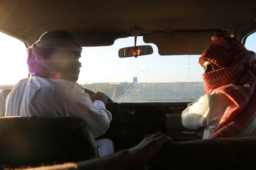 """Saudi men are seen in a vehicle as they perform a stunt known as """"sidewall skiing"""" in Tabuk"""