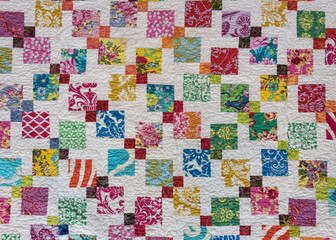 Multi colored quilt squares scattered across white
