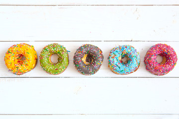 Sweet and colorful donuts on white wooden table with copy space. Top view
