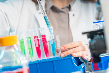 Young woman in scientific lab with pipette and chemicals in test tubes