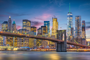 New York City, USA skyline on the East River with Brooklyn Bridge at dusk.